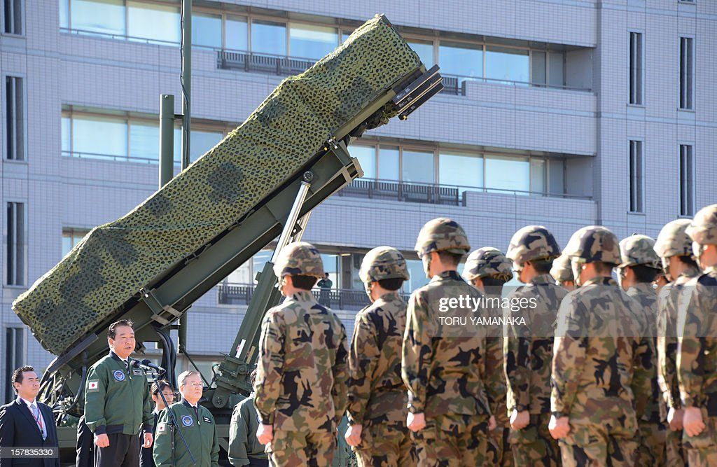 Japanese Prime Minister Yoshihiko Noda (2nd L) gives a speech as he addresses soldiers while in front of a Patriot Advanced Capability-3 (PAC-3) missile launcher at the Defence Ministry in Tokyo on December 7, 2012. Japan on December 7 issued the order to shoot down a North Korean rocket if it threatens the nation's territory, the top government official said. Tokyo has readied surface-to-air missiles in and around Tokyo, as well as in Okinawa, and is putting its armed forces on standby ahead of Pyongyang's planned missile launch. AFP PHOTO / Toru YAMANAKA