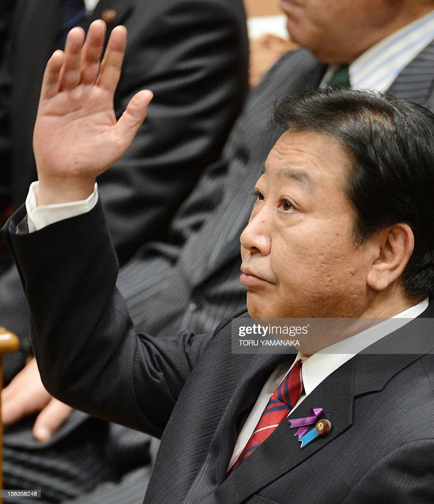 Japanese Prime Minister Yoshihiko Noda raises his hand before he answers questions during a one-by-one debate with President of the main opposition Liberal Democratic Party (LDP) Shinzo Abe at the lower house on November 14, 2012. Noda said on November 14 he will dissolve parliament on November 16 to hold an election if his opponents play ball on reforming the electoral system. AFP PHOTO / Toru YAMANAKA