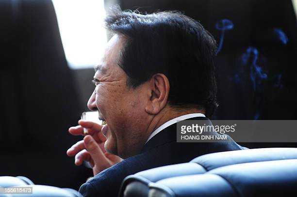 Japanese Prime Minister Yoshihiko Noda smokes during a break as he attends the 9th Asia-Europe summit being held in Vientiane on November 6, 2012....
