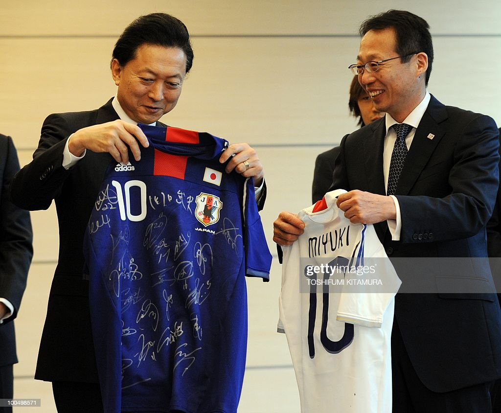 Japanese Prime Minister Yukio Hatoyama (L) looks at a signed uniform received from Japan National Football team head coach Takeshi Okada (R) at Hatoyama's official residence in Tokyo, on May 25, 2010 while Okada holds a uniform for Hatoyama's wife, Miyuki. The team will leave here on May 26 for a Switzerland training camp before joining the 2010 FIFA World Cup South Africa.