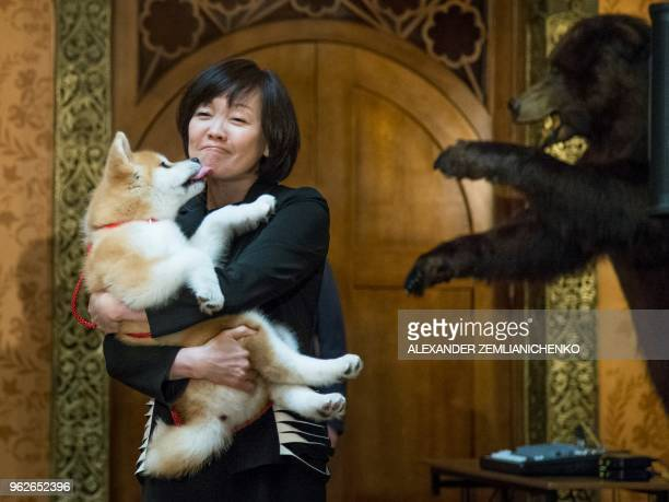 Japanese Prime Minister's wife Akie Abe holds an Akita Inu puppy named Masaru in her ams during their official visit to Moscow Russia on May 26 2018...