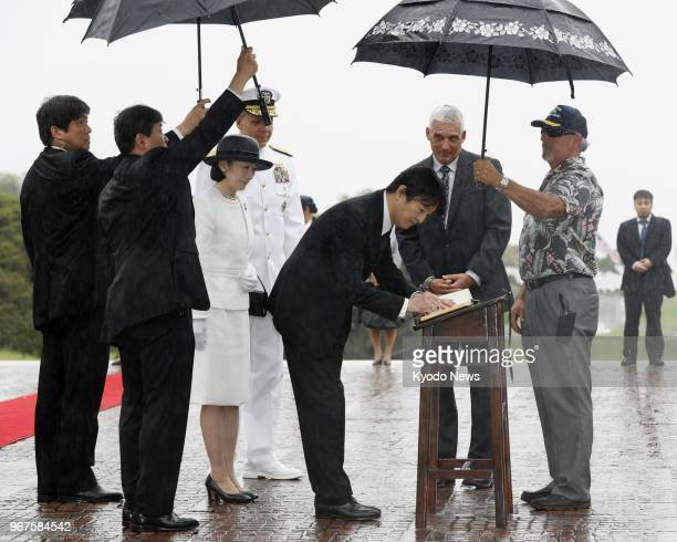 Japanese Prince Akishino alongside his wife Princess Kiko signs a guestbook after paying tribute at the National Memorial Cemetery of the Pacific in...