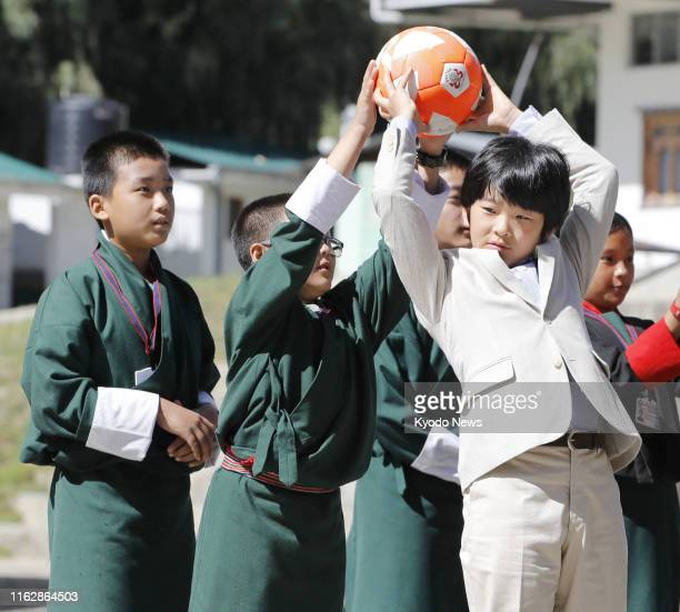 Japanese Prince Hisahito the only son of Crown Prince Fumihito and Crown Princess Kiko plays with a ball with local students in Thimphu the capital...