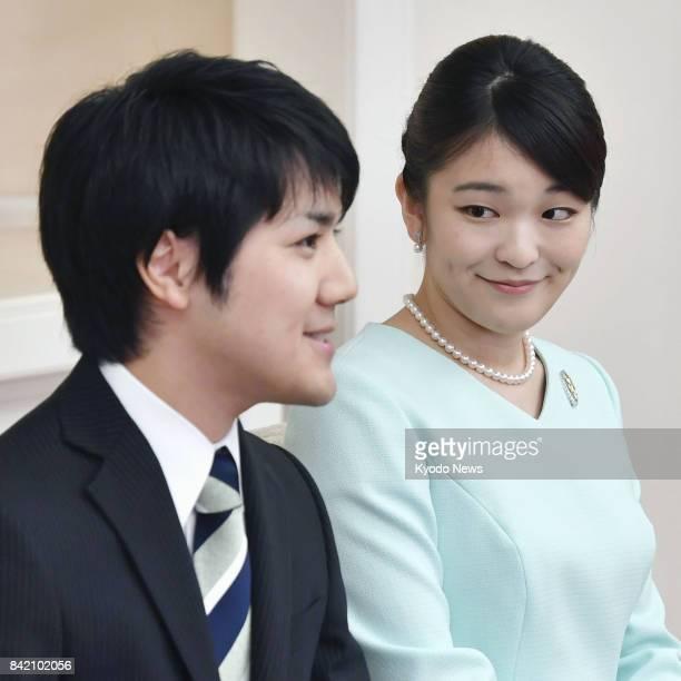 Japanese Princess Mako the eldest granddaughter of Emperor Akihito and Empress Michiko looks at her longtime boyfriend Kei Komuro during a news...