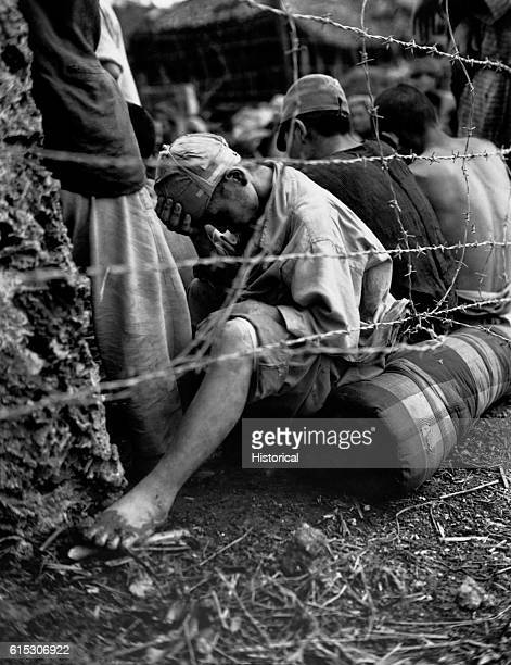Japanese prisoner of war sits with forhead in hand behind a barbed wire fence, after capture with 306 others within 24 hours of the Okinawa battle by...