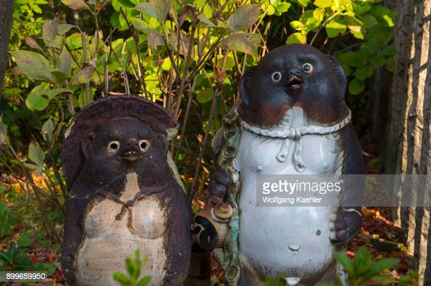 Japanese raccoon dog statues in the Japanese garden of a restaurant in Kyoto Japan
