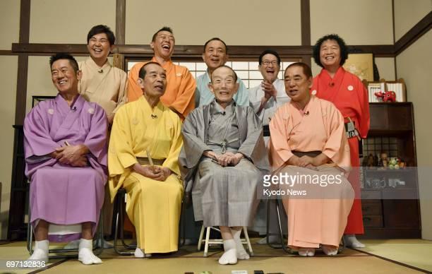 Japanese 'rakugo' comedic storyteller Utamaru Katsura surrounded by fellow members of longrunning TV program 'Shoten' speaks to reporters in Tokyo on...