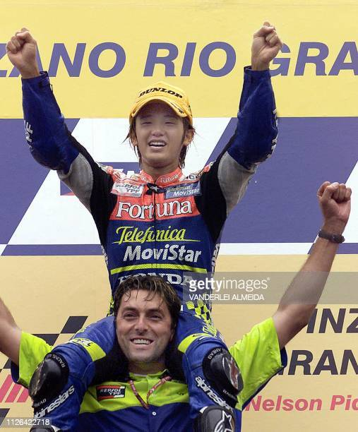 Japanese rider Daijiro Katoh celebrates his victory sitting on the shoulders of his teammate Fabrizio Cecchini 03 November 2001 after winning the...