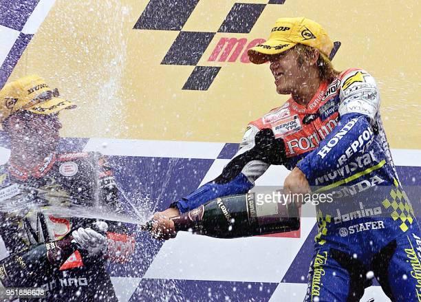 Japanese rider Daijiro Katoh sprays champagne on Italian Marco Melandri to celebrates his victory 03 November 2001 after winning the Rio's 250cc FIM...