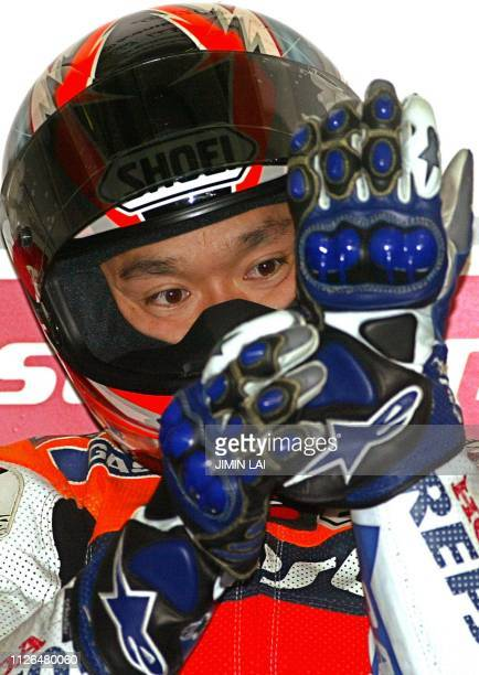 Japanese rider Tohru Ukawa of Repsol Honda puts on his gloves at the pits of the Sepang International Circuit during the first practice session of...