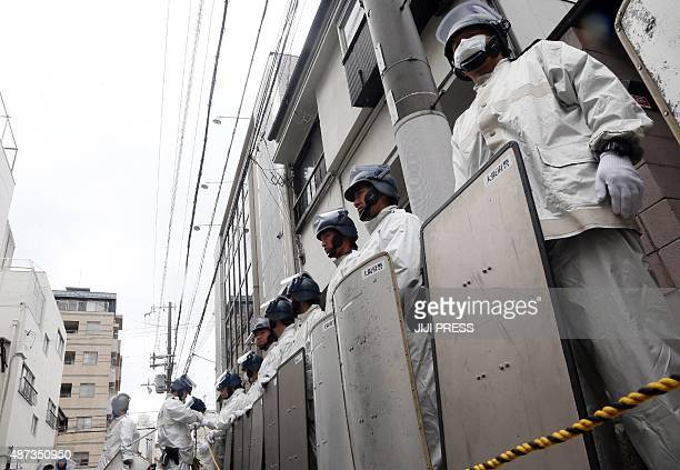 Japanese riot police stand guard outside of the headquarters of the 'yakuza' crime syndicate the 'Yamakengumi' during a police raid on the building...