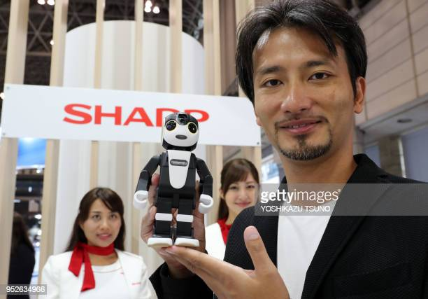 Japanese robot creator Tomotaka Takahashi displays a robot smartpone RoBoHoN started to sell this May from Sharp at the CEATEC Japan 2016 in Chiba...