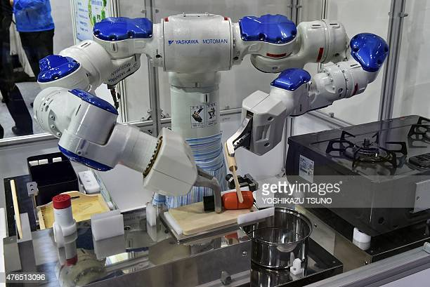 Japanese robot giant Yaskawa Electric's industrial robot Motoman performs a cooking demonstration at the International Food Machinery and Technology...