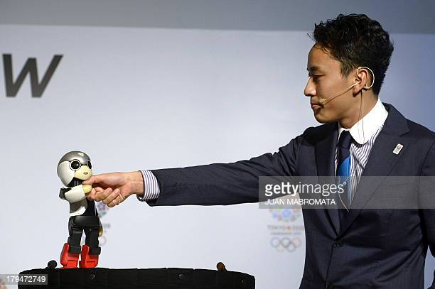 Japanese robot Mirata and Japanese double fencing silver medallist Yuki Ota shake hands during a news conference given by IOC member and President of...