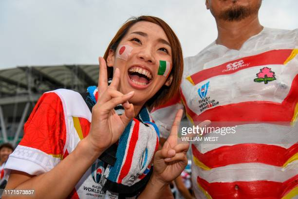 Japanese rugby fans one with the national team's jersey painted on his upper body arrive for the Japan 2019 Rugby World Cup Pool A match between...