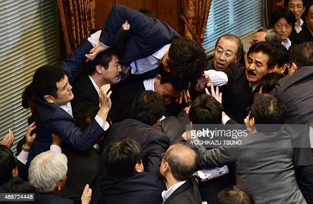Japanese ruling and opposition lawmakers scuffle at the Upper House's ad hoc committee session for the controversial security bills at the National...