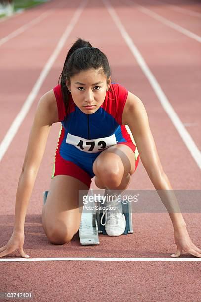 若い女性ランナーにスターティングブロックで競馬場