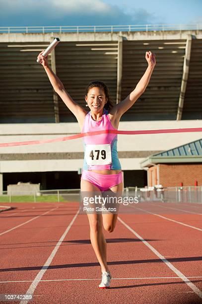 若い女性ランナー、バトンに輝くレース - 決勝線 ストックフォトと画像