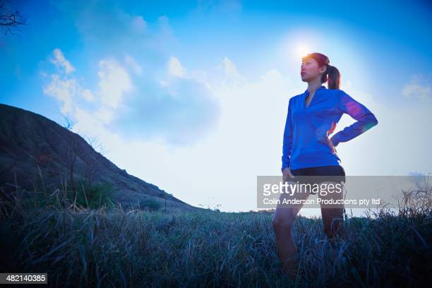 Japanese runner with headlamp in rural field