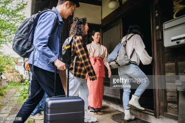 日本の旅館経営者がビルに入ると到着する新しいゲストを歓迎 - 宿屋 ストックフォトと画像