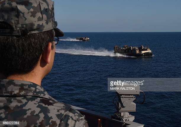 Japanese sailor watches Japanese LCAC from the Japan Maritime Self-Defense Force ship JS Hyuga during the Dawn Blitz 2015 exercise off the coast of...