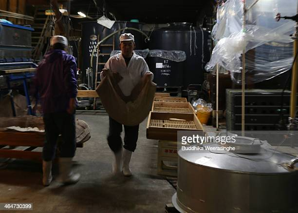 Japanese sake brewery workers transport steamed rice to put to in sake barrels for fermenting at Tanaka Sake Brewery on January 24 2014 in Himeji...