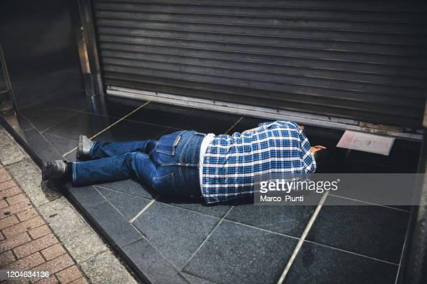 歩道で眠っている日本人サラリーマン - ノックアウト ストックフォトと画像