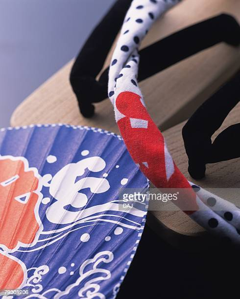 Japanese sandals, Japanese fan and towel, high angle view, gray background