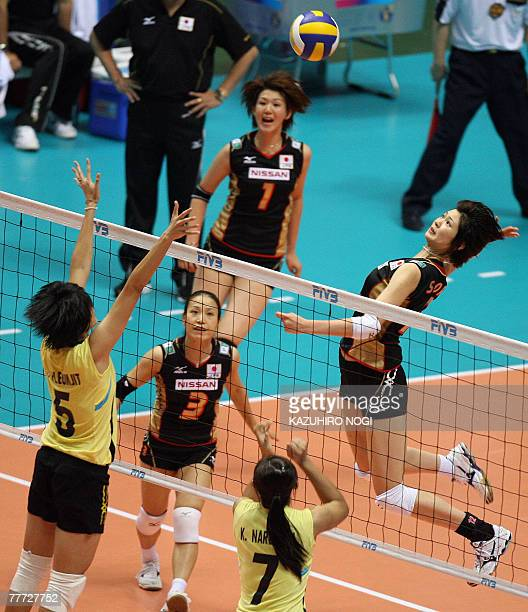 Japanese Saori Kimura jumps to spike the ball over Thailand's blockers, Pleumjit Thinkaow and Narumon Khanan during their second round match of the...