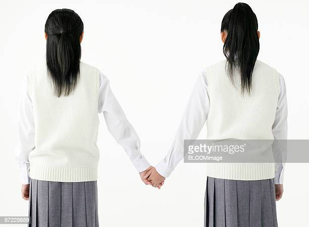 japanese school girls holding hand - asian twins stock photos and pictures