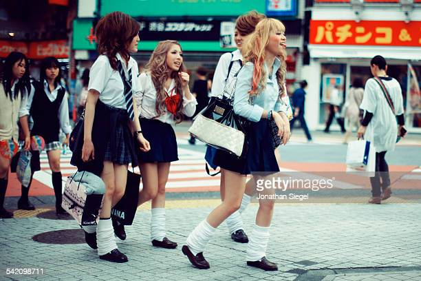 Japanese school girls with funky and crazy hair styles and mini skirts crossing the street in Shibuya, Tokyo.
