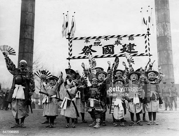 Japanese schoolchildren and teacher in Samurai armour honouring the Japanese Emperor and waving hands
