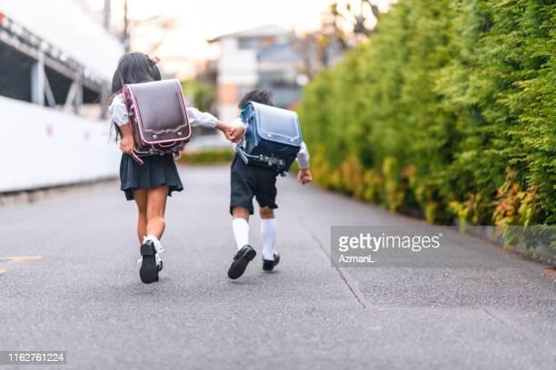 japanse schoolkinderen houden van handen en hardlopen - uniform stockfoto's en -beelden