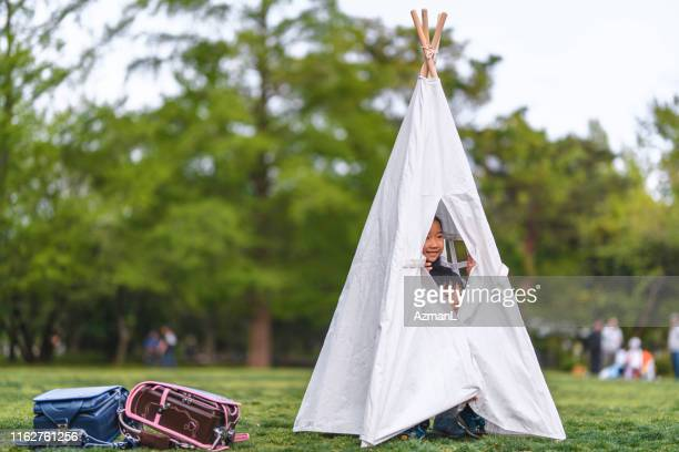 japanese schoolchildren playing in teepee at public park - teepee stock pictures, royalty-free photos & images