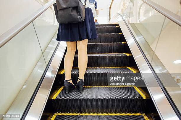 japanese schoolgirl in a skirt riding on escalator - japanese short skirts stock photos and pictures