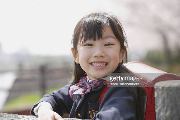 Japanese schoolgirl smiling and looking at camera