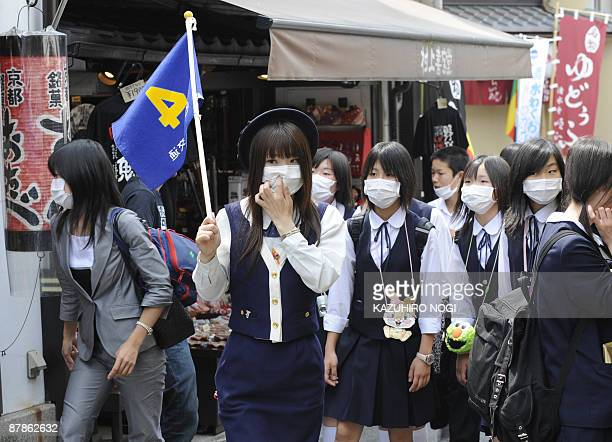 Japanese schoolgirls wearing facemasks are led by a guide on their way to the popular Kiyomizu temple in Kyoto during a school excursion on May 20,...