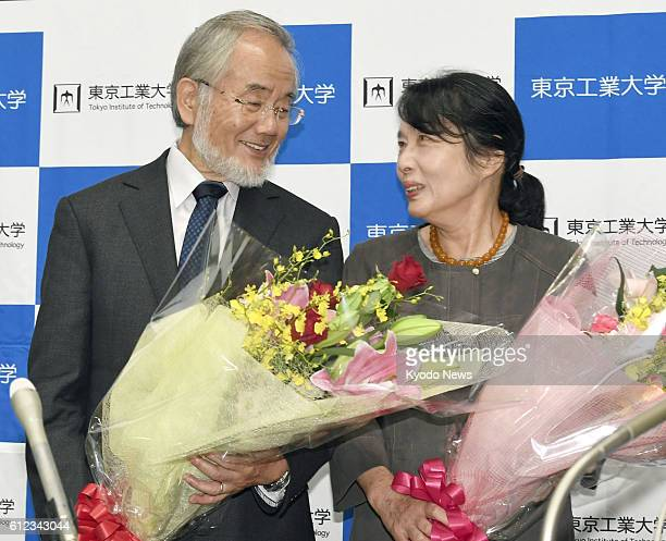 Japanese scientist Yoshinori Ohsumi and his wife Mariko pose for photos with flowers during a press conference at the Tokyo Institute of Technology...
