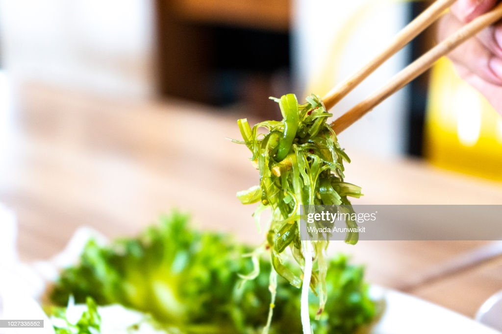 Japanese seaweed salad in chopsticks ready to eat. : Stock Photo