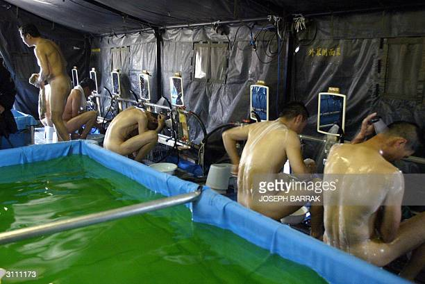 Japanese Self Defence Force soldiers bath inside an improvised sento 19 March 2004 in their new camp still under construction in the southern town of...