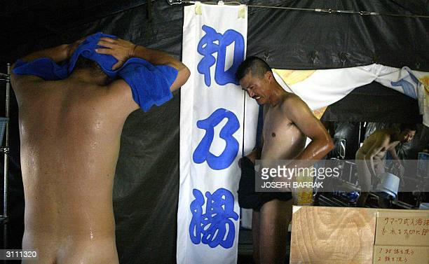 Japanese Self Defence Force soldiers bathe inside an improvised sento 19 March 2004 in their new camp still under construction in the southern town...