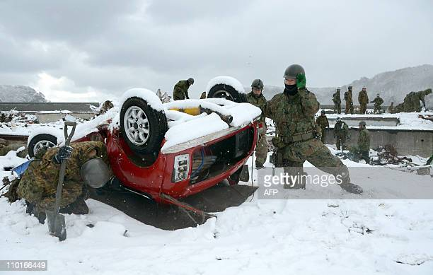Japanese Self Defence Force soldiers inspect a vehicle overturned by the March 11 tsunami in Miyako in Iwate prefecture on March 16 2011 Japan's...