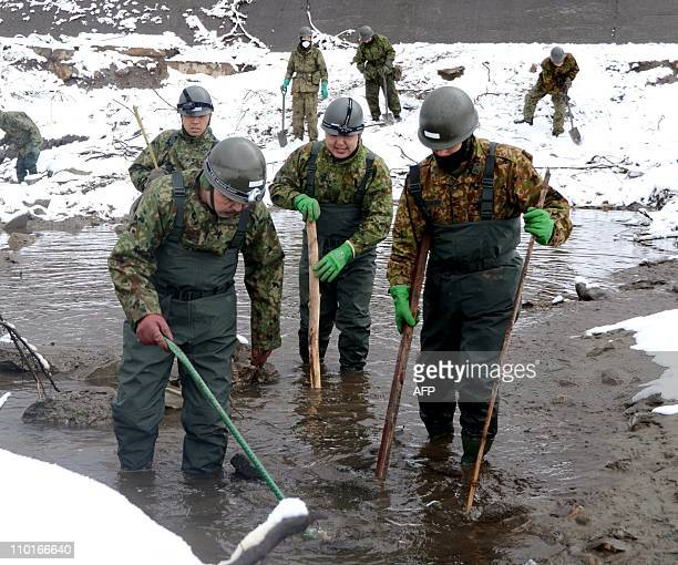 Japanese Self Defence Force soldiers search for people missing from the March 11 tsunami in a river bed in Miyako in Iwate prefecture on March 16...