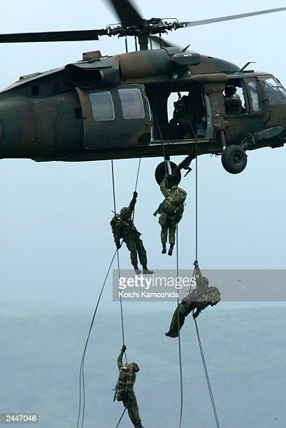 Japanese Self Defense Force members rappel from a combat helicopter during a training drill August 30 2003 in Gotenba Japan Fears are growing in...