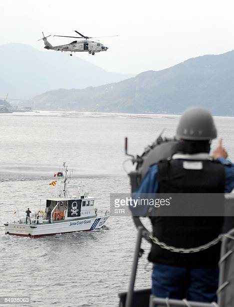 A Japanese SelfDefence Force's helicopter hovers above a Japanese coast guard boat marked as a 'suspected pirate's ship' off the coast of the Kure...