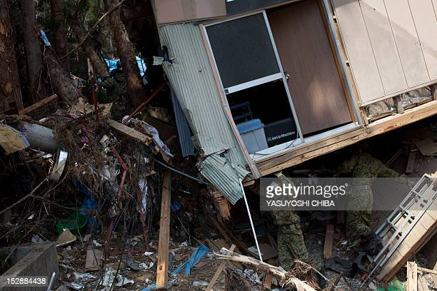 Japanese SelfDefence forces search under a tsunami destroyed house in Kesennuma city Miyagi prefecture on April 14 2011 Japan's seismologists were so...