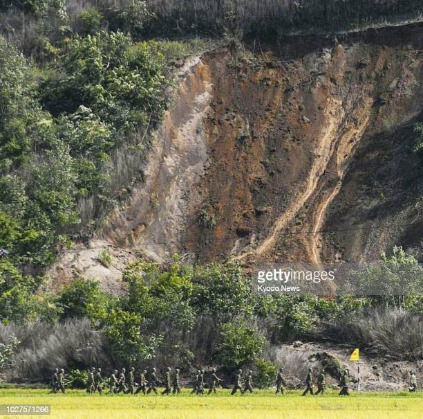 Japanese Self-Defense Forces personnel head for the site of a landslide in Atsuma, Hokkaido, to search for missing persons on Sept. 6 after a strong...