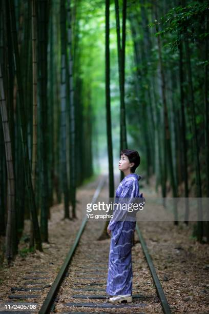 japanese senior lady in yukata. she stands in a bamboo forest with an abandoned track. - 鳥取県 ストックフォトと画像