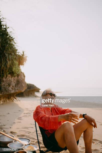 japanese senior man having fun at beach campsite - ippei naoi stock pictures, royalty-free photos & images