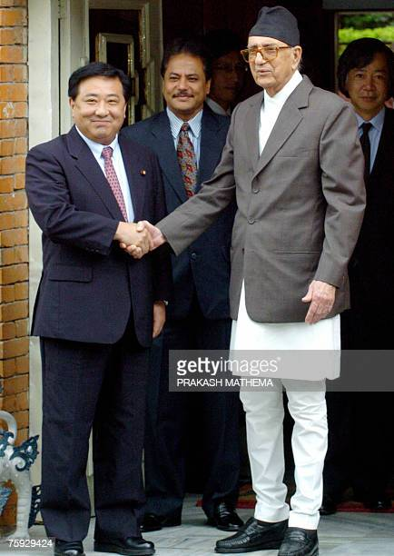 Japanese Senior ViceMinister for Defense Takahide Kimura shakes hands with Nepalese Prime Minister Girija Prasad Koirala during a meeting in...